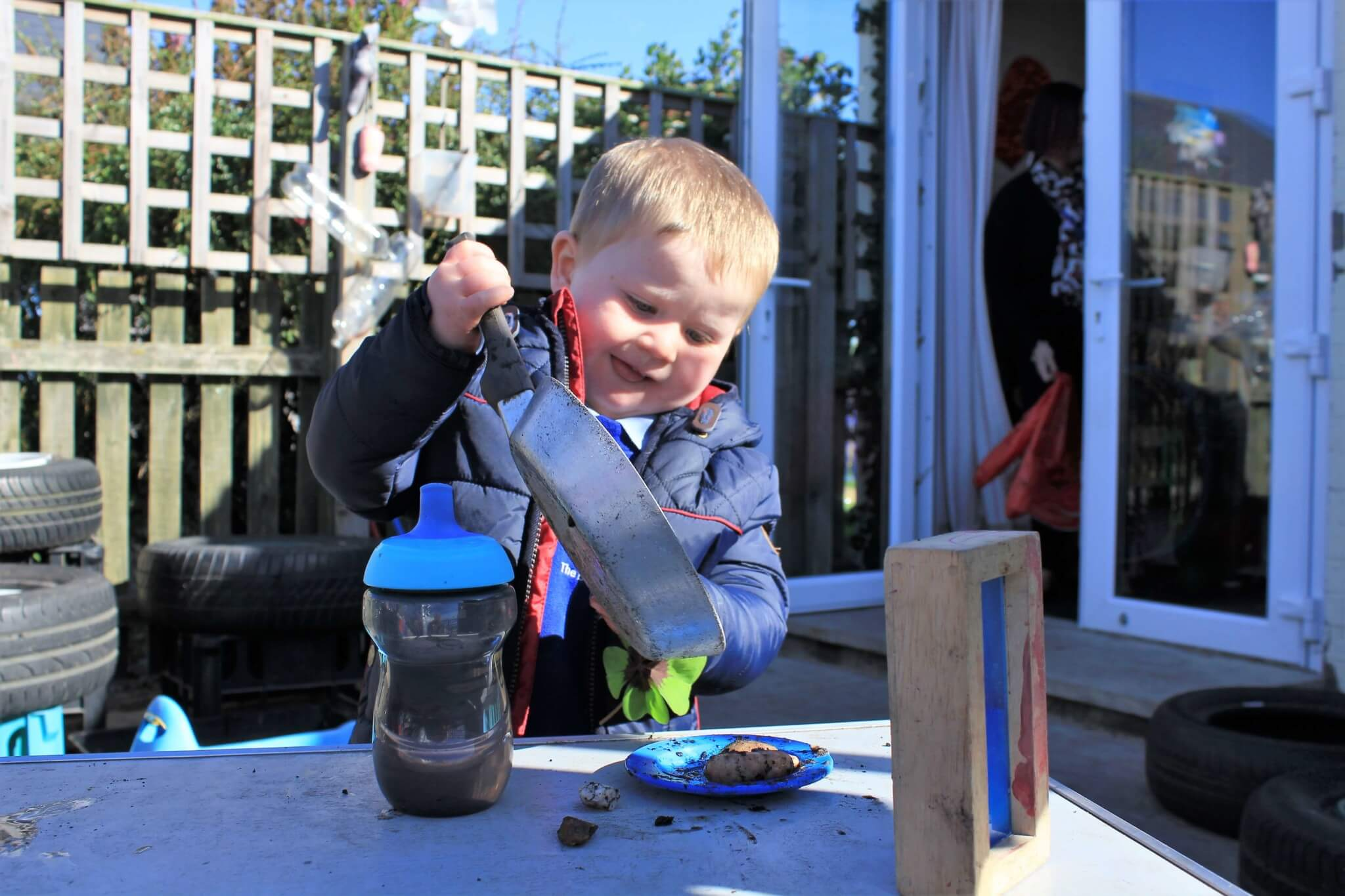 Young person playing with a 'mud kitchen' at Town Tots pre-school