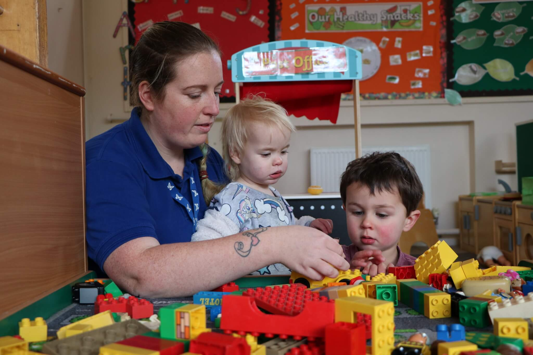 Staff and children playing with Lego at Ditchingham Day Nursery