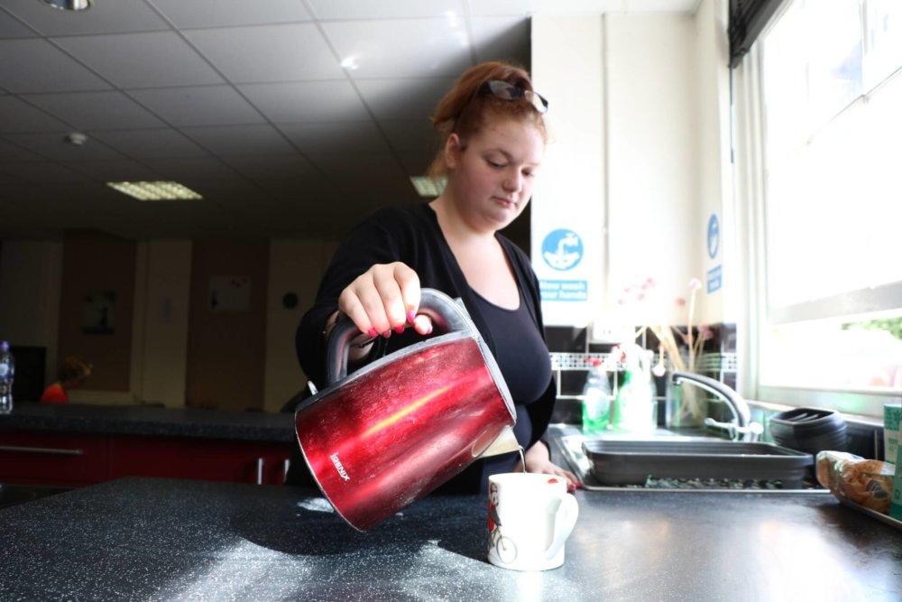 Young Person making coffee at an accommodation centre